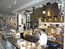 A broad, bright kitchen space with mostly silver and gray tones and warm yellow lights and several chefs at various stations preparing food