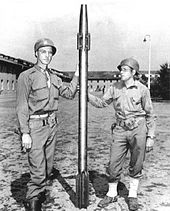 Two soldiers in US Army uniforms hold between them a long, slim projectile that is somewhat taller than them, with a finned tail