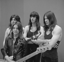 A black and white photo of Quatro and her unnamed band. Quatro is holding her bass guitar, standing, and wearing a black leather jacket; her three taller and long-haired male bandmembers are standing behind her wearing dark tee shirts.