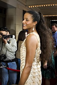 A woman wearing a tan/gold dress. She is looking toward the left, while smiling toward cameras.