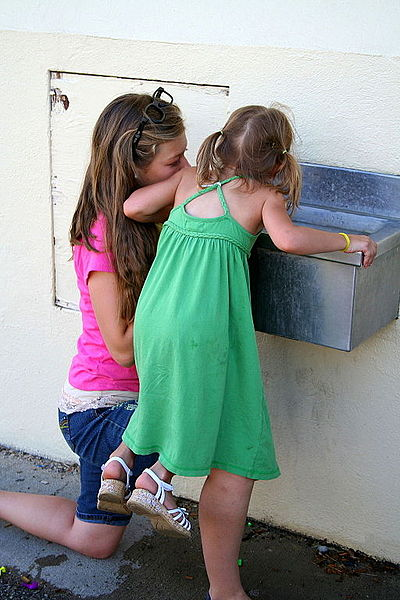 File:Teen helping little child at drinking fountain (7994609665).jpg