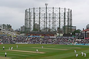 A cricket match in progress; gasholders are visible in the background