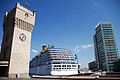 The Torretta clock tower in the Port of Savona against background of -Costa Atlantica- cruise ship. Savona, Liguria region, Italy.jpg