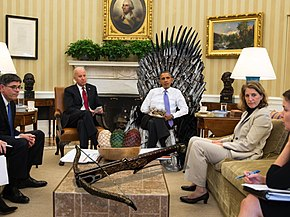 President Obama sits on a digitally-added Iron Throne in the Oval Office of the White House, surrounded by other people