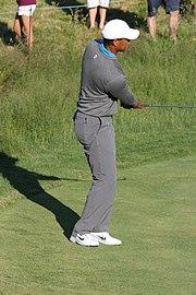 Le golfeur termine son geste avec son club à l'horizontal et les yeux vers sa balle.