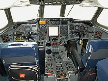 "The flight deck of a jet airliner with many instruments and controls. Two pilots' seats have small bags hanging on them, one showing the words ""British European Airways""."