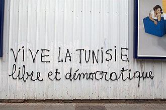 "African French - French-language graffiti on Avenue Habib Bourguiba in Tunis, in March 2012. The graffiti says: ""LONG LIVE TUNISIA (Vive la Tunisie), free and democratic""."