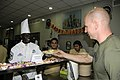 U.S. Air Force Chief Master Sgt. Roy Wicks, left, the command chief of the 379th Air Expeditionary Wing, hands a plate of food to a Service member during a Thanksgiving Day celebration at an undisclosed location 131128-F-QD538-037.jpg