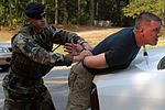 U.S. Air Force Staff Sgt. Barry Elkins, left, with the 314th Security Forces Squadron, apprehends Staff Sgt. Adam Bennet after a simulated gate run during a ROCKEX exercise at Little Rock Air Force Base (AFB) 070815-F-YN203-006.jpg