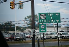 An intersection in a business area with a green sign reading Route 70 west Lakehurst with two right arrows