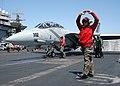 US Navy 040604-N-3986D-018 Aviation Ordnanceman 3rd Class Thomas Blair Jr. of Houston, signals for the aircrew to raise their hands while ordnancemen check all ordnance on an F-14B Tomcat.jpg