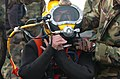 US Navy 050210-N-3541A-010 Chief Petty Officer Wes Mason, a Navy diver, performs final checks on his dive helmet before dive operations commence for a downed helicopter.jpg