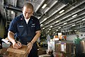 US Navy 050721-N-3136P-006 Storekeeper 1st Class William Samson of Vallejo, Calif., marks a package during the sorting of more than 900 pounds of mail in the hangar bay aboard USS Kitty Hawk (CV 63).jpg