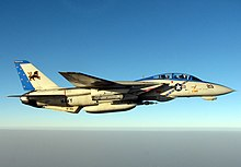Pale gray jet aircraft flying over water towards right, perpendicular to the camera. Horizon located two-thirds down the photo. Sky made up of two shades, dark blue covers the top, blending with a lighter shade until it is almost white above horizon