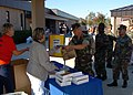 US Navy 051026-N-9583M-001 Navy Exchange (NEX) employees hand out free pre-paid cell phones with 70 minutes of talk time.jpg