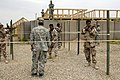 US Navy 060412-N-4614W-005 Army Sgt. Randal Boyd assigned to Headquarters Company, 1st Battalion, 327th Infantry Regiment, observes how Iraq Army soldiers from 5th Battalion, assault a glasshouse during military operations on.jpg