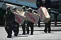 US Navy 060630-N-6106R-084 Squadron personnel from the Diamondbacks of Strike Fighter Squadron One Zero Two (VFA-102) carry boxes across the flight deck of USS Kitty Hawk (CV 63).jpg