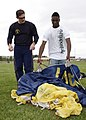 US Navy 090528-N-5366K-050 Chief Special Warfare Operator (SEAL) William Davis, assigned to the U.S. Navy Parachute Team the Leap Frogs, shows a student how to pack his parachute after parachuting into F.J. Turner High School i.jpg