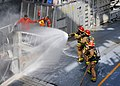 US Navy 110922-N-MW330-057 First responders use a fire hose to extinguish a simulated fire represented by two flags held by Damage Controlman 1st C.jpg