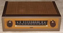 A small rectangular brown box with a metallic coppery top on a beige carpet. On its front are two dials and a tuner with a range between 88 and 108