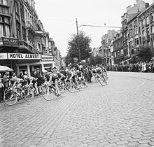A group of cyclists passing through a city, watched by many spectators