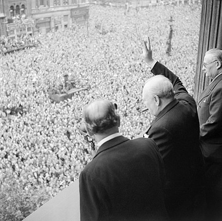 Churchill waving the Victory sign to the crowd in Whitehall on the day he broadcast to the nation that the war with Germany had been won, 8 May 1945. Ernest Bevin stands to his right. Winston Churchill waves to crowds in Whitehall in London as they celebrate VE Day, 8 May 1945. H41849.jpg
