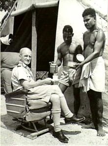 Caucasian man in light-coloured military uniform seated outside tent and being served tea by two indigenous men in light-coloured shorts and loincloth