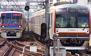 Tokyo subway - Top: The logos of the Tokyo Metro and Toei Subway  Bottom: Toei 6300 series (left) and Tokyo Metro 10000 series (right) trains at Musashi-Kosugi Station