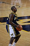A basketball player in a dark blue uniform is eying a shot with the basketball in his hands at his waist.