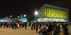 Night view of modern building, with many people walking outside