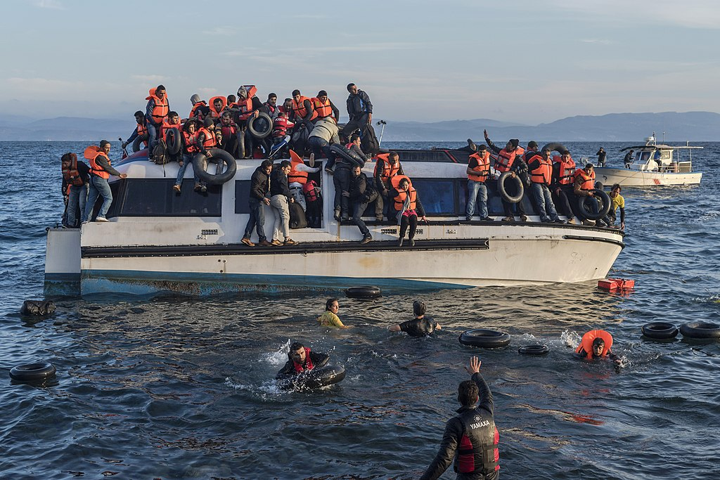 A small boat in water, with land on the horizon behind. Many people are on its outside in orange life jackets, some carrying inner tubes as well. A few are in the water swimming toward the camera. In the foreground a man in a red and back wetsuit has his hand out to them.