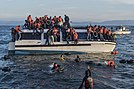 Syrian and Iraqi immigrants getting off a boat from Turkey on the Greek island of Lesbos. A small boat in water, with land on the horizon behind. Many people are on its outside in orange life jackets, some carrying inner tubes as well. A few are in the water swimming toward the camera. In the foreground a man in a red and black wetsuit has his hand out to them.