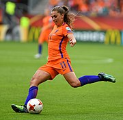 Footballer Lieke Martens prepares to kick the ball with her outstretched left foot.