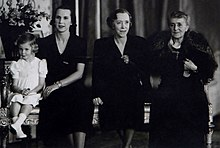 quatre générations féminines posent côté à côte. De gauche à droite on voit une fillette assise et vêtue de clair, puis trois femmes vêtues de sombre