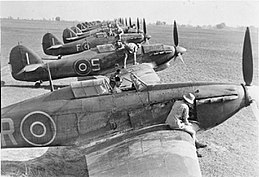 Side view of eleven World War II fighter planes parked in a very large field. Soldiers in khaki uniform, wearing shorts, climb atop or sit inside all of them making repairs.