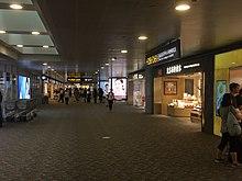 Sur cette image, vous pouvez voir des magasins et une enseigne de salle de bain situés dans un couloir du terminal 2.