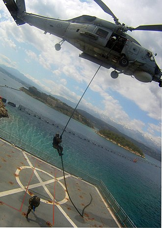 NATO Maritime Interdiction Operational Training Centre - Image: A member of an Algerian navy boarding team fast ropes out of a Hellenic Navy S 70B 6 Aegean Hawk helicopter assigned to the 2nd Squadron onto the training ship Aris (A 74) at the NATO Maritime Interdiction 120517 N QD416 196