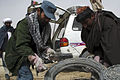 Afghan policeman Khudai Dad, left, deputy district chief of police, Khas Uruzgan, helps a recently reintegrated Taliban fighter load razor wire into a vehicle at Khas Uruzgan district, Uruzgan province 120304-N-JC271-110.jpg