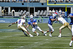In an American football game, a runner with the ball faces a defender while a blocker locks with another defensive player.