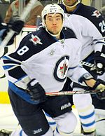 A Caucasian hockey player. He is wearing a white jersey with blue shoulders with a jet over a maple leaf inside of a circle for the logo. He is starting his skating stride with his eyes looking towards the camera.