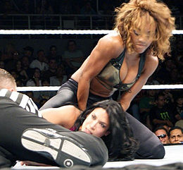 An African-American woman with dark curly hair, wears a camouflage dress with a red belt and fur trim on the shoulders, white wrestling boots and knee-high red stockings. A blonde woman, wearing a black hooded jacket is visible in the background, standing with her back to the camera.