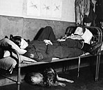 American volunteers, Flight Sergeant Bill Kelly (left) and Flying Officer Osbourne of No. 121 (Eagle) Squadron, RAF, at rest in the Dispersal Hut at Rochford airfield in Essex during 1942. D9518.jpg