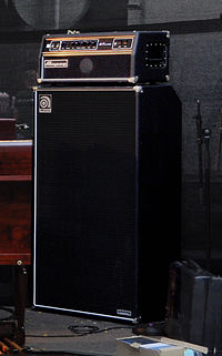 A large bass speaker cabinet with an amplifier unit sitting on top of it.