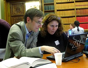 The photo shows a man and a woman sat at a competer in a library discussing how to edit Wikipedia