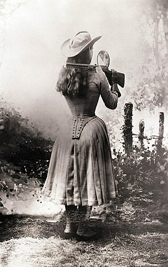 Annie Oakley - Annie Oakley shooting over her shoulder using a hand mirror.