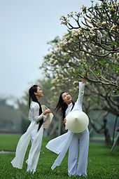 Photograph of two girls wearing a traditional Vietnamese white school uniform, the áo dài--both are holding the nón lá, a conical hat
