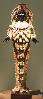 Artemide Efesia risalente al II secolo d.C. La statua rappresenta l'immagine cultuale presente nel tempio di Artemide a Efeso. Originariamente l'immagine cultuale era in ebano, ricoperta di vesti preziose e gioielli periodicamente rinnovati per mezzo di elaborate cerimonie. Qui l'immagine veste un chitone (?????) stretto sotto un grembiule (?????????) legato da una cintura. Sul busto propendono un insieme di