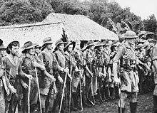 Rangée de soldats vêtus légèrement et crosse du fusil au sol. Un soldat ou officier se trouve hors du rang. Deux toits de chaume et une végétation apparemment tropicale en fond.