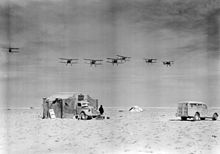 A group of six biplanes flies in formation over the desert