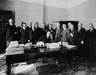 R. B. Bennett - Prime Minister Bennett, surrounded by members of the Cabinet, speaking by telephone to Sir George Perley, Canadian Cabinet minister, at the British Empire Trade Fair at Buenos Aires.